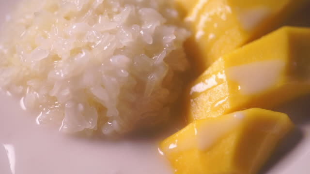 Tilt up camera of Sweet mango with sticky rice served on a white plate.