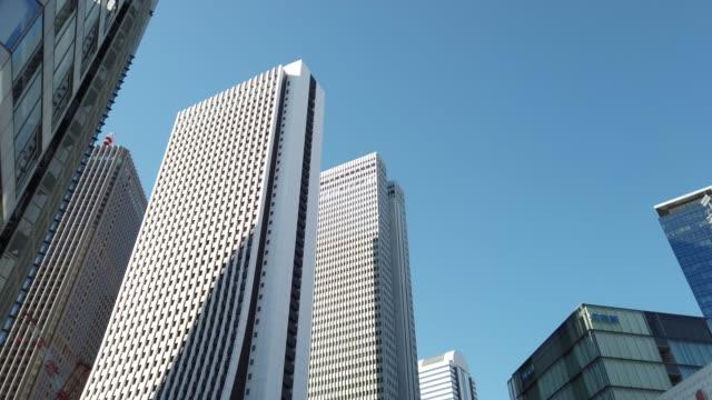 vídeos de stock, filmes e b-roll de incline para cima. fundo do escritório da arquitectura da cidade em shinjuku em tokyo, japão. - inclinação para cima