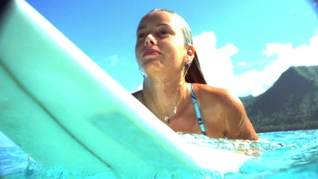 Tilt up close up female surfer emerging with surfboard / tilt down beneath surface of water