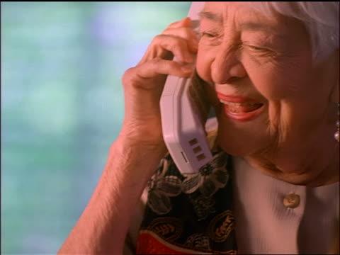 tilt up close up hispanic senior woman talking on cordless telephone + laughing - sladdlös telefon bildbanksvideor och videomaterial från bakom kulisserna