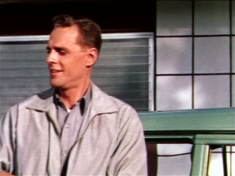 1959 tilt up close up man exiting + closing door of green colored vehicle parked in front of house / industrial - 1959 stock-videos und b-roll-filmmaterial