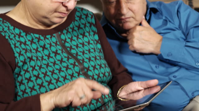 vídeos de stock e filmes b-roll de tilt up, close up of a husband and wife talking and looking concerned, while going through images on a touchscreen tablet - idoso na internet