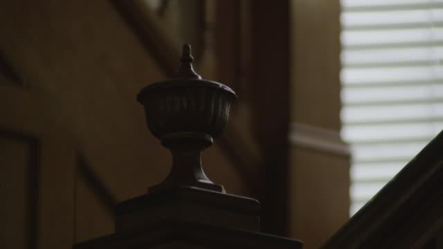 Tilt up, close up vintage door knob, old oak door slightly ajar. Dark and creepy.