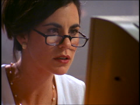 tilt up close up woman wearing reading glasses working on computer + nodding head at screen - reading glasses stock videos & royalty-free footage