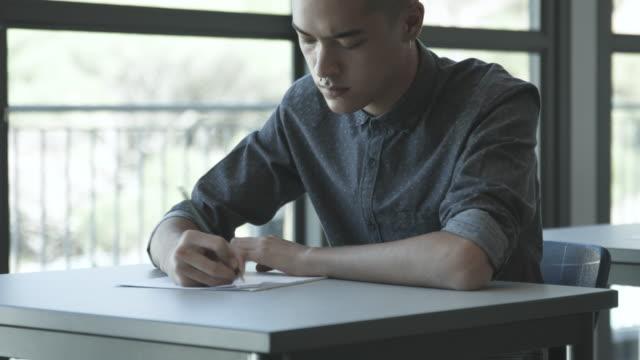 vídeos y material grabado en eventos de stock de tilt up, college student writes at table - peladas