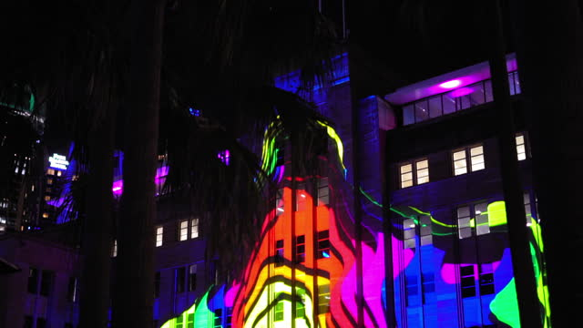 tilt up: colorful psychedelic light pattern on building at night - sydney, australia - art stock videos & royalty-free footage
