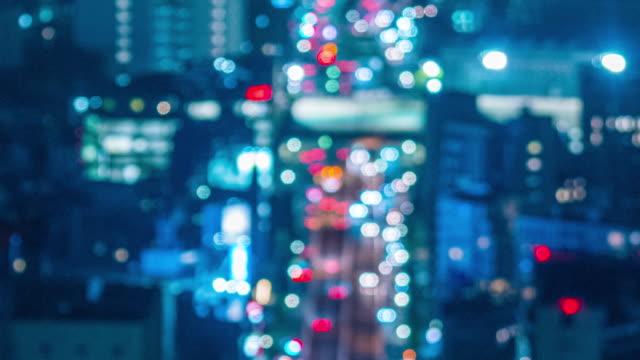 stockvideo's en b-roll-footage met 4k tilt up defocused bokeh cirkel licht wazig nacht timelapse van het verkeer stadsgezicht in tokio, japan - de weg voorwaarts