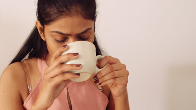tilt up down from the face of a gorgeous young lady sipping a drink and working with her well manicured brown nail polished finger nails hands on a black keyboard of a communication device - coffee drink stock videos & royalty-free footage