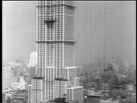 b/w 1930 tilt up empire state building under construction / nyc - empire state building video stock e b–roll