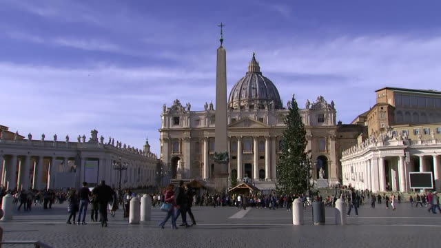 tilt up establishing shot of police car driving past vatican obelisk christmas tree and st peter's basilica in st peter's square - crime or recreational drug or prison or legal trial video stock e b–roll