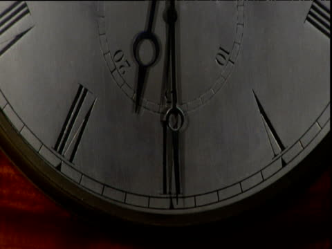 tilt up face of antique grandfather clock with ticking seconds hand - 大時計点の映像素材/bロール