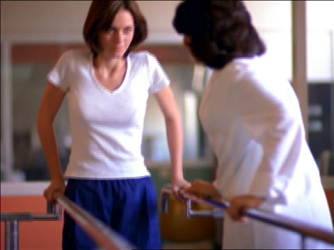 tilt up female doctor helping female patient walk slowly in rehab / physical therapy