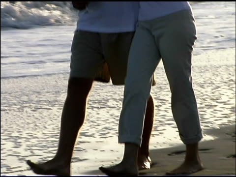 tilt up follow of a couple walking together in the ocean surf. they have their arms around each other and are carrying wine glasses. - see other clips from this shoot 1135 stock videos & royalty-free footage