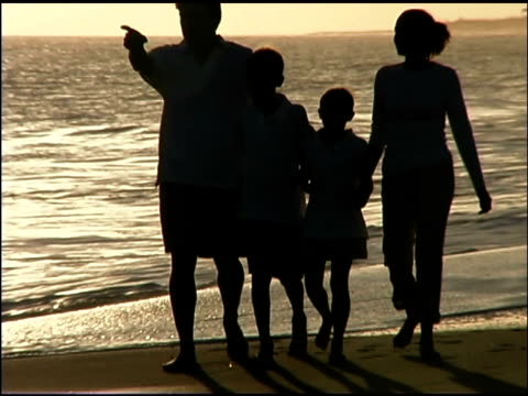 tilt up follow silhouette of a family walking together at sunset on the beach. - see other clips from this shoot 1135 stock videos & royalty-free footage