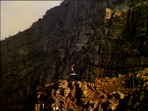 tilt up following cable car ascending table mountain, south africa - felswand stock-videos und b-roll-filmmaterial