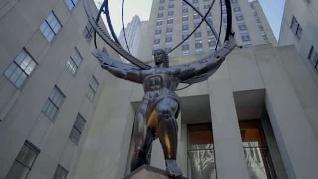 tilt up footage of metallic atlas statue against rockefeller centre in city, low angle view of sculpture by modern building in city - new york city, new york - rockefeller center video stock e b–roll