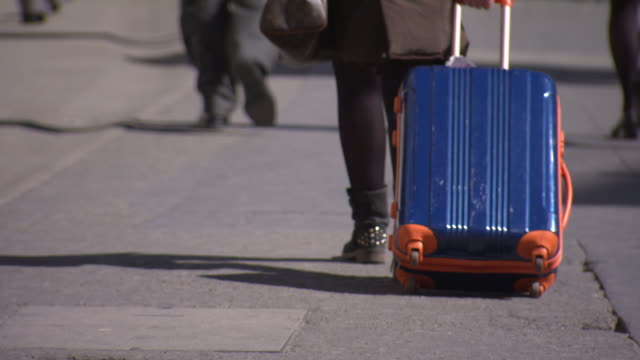 tilt up from a blue and orange suitcase being pulled along pavement, london, uk. - pulling stock videos & royalty-free footage