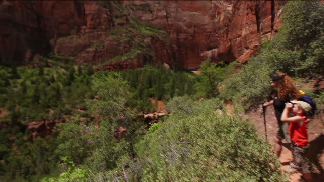 tilt up from a mother and her son looking out at view to the top of rocky mountains against blue skies in zion national park - zion national park stock videos & royalty-free footage