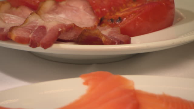 tilt up from a seafood and quail egg platter to bacon and cooked tomatoes. - group of objects stock videos & royalty-free footage