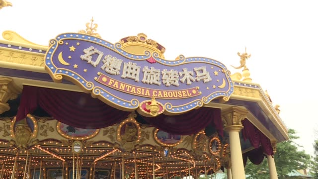 tilt up from a water reflection of storybook castle to visitors walking over a bridge past the castle at walt disney co's shanghai disneyland theme... - carousel horse stock videos and b-roll footage