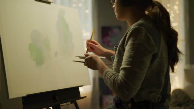 vídeos de stock, filmes e b-roll de tilt up from art supplies to woman listening to headphones and painting on canvas / cedar hills, utah, united states - pintor artista