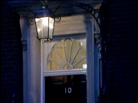 tilt up from black door of 10 downing street to illuminated window of upper floor room - downing street stock videos & royalty-free footage