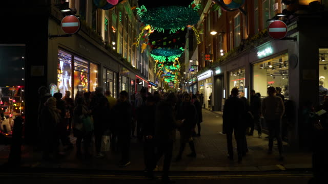 Tilt up from Carnaby Street busy with shoppers to carnival style Christmas decorations