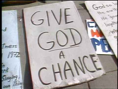 "tilt up from close up of ""give god a chance"" poster to male hippie lying on sidewalk - 1972 stock videos & royalty-free footage"