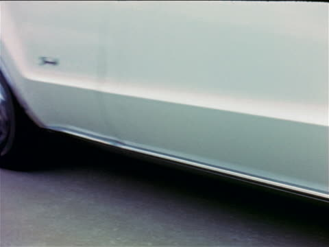 1968 tilt up from close up of oldsmobile toronado driving away on test track / industrial - 1968 stock videos and b-roll footage
