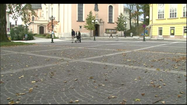 vídeos de stock e filmes b-roll de tilt up from cobbled town square to parish church, bad ischl, austria - patio