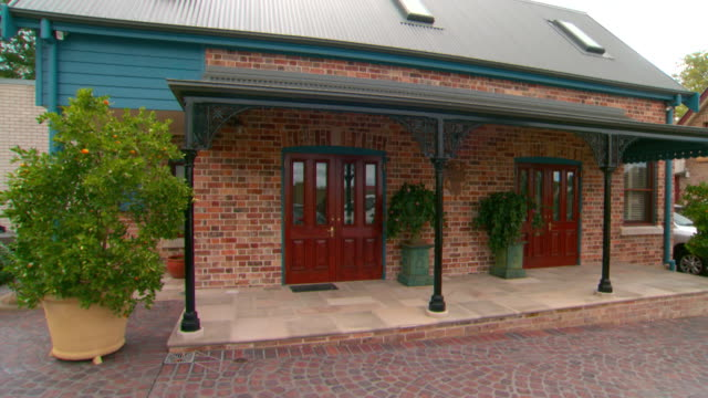 tilt up from cobblestone paving to cottage frontage two double doors awning decorative plants french style pavers on the patio skylights on roof - awning stock videos and b-roll footage