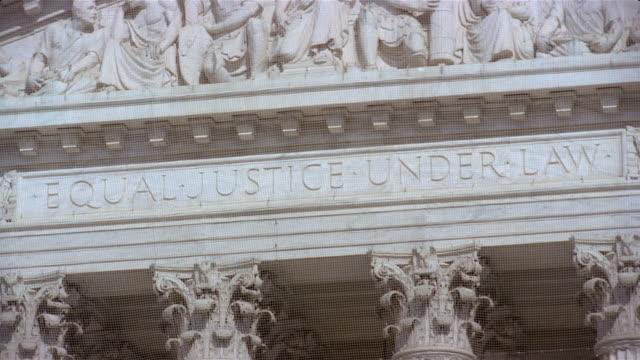 tilt up from corinthian capitals to architrave incised 'equal justice under law' to frieze decorated with bas-reliefs above entrance to us supreme court building / washington, dc - architrav stock-videos und b-roll-filmmaterial