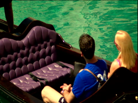 Tilt up from couple in gondola to gondolier wearing traditional Italian outfit Venice Resort Las Vegas