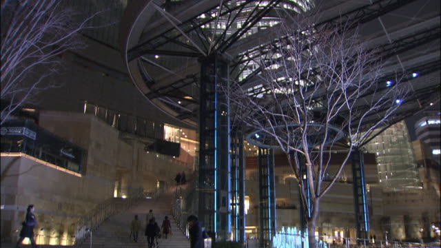 tilt up from entrance, to illuminated arts centre building of roppongi hills leisure complex - 2003 stock videos and b-roll footage
