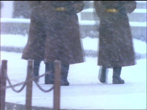tilt up from feet of 3 Russian soldiers marching during snowstorm / Moscow
