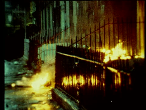 vídeos de stock e filmes b-roll de tilt up from fire burning on steps door and windows of british embassy from petrol bombs thrown by protestors angry at bloody sunday shootings dublin... - petroleum