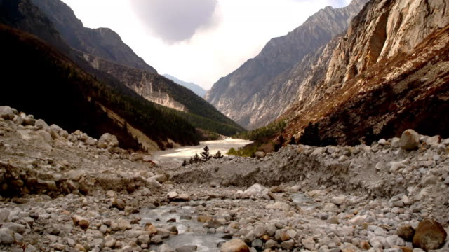 Tilt up from flowing water of a Ganges tributary to a valley in Uttarakhand, India.