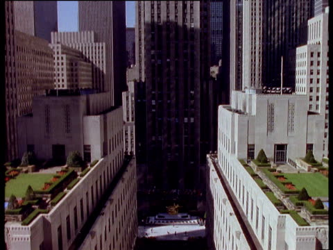 vídeos de stock, filmes e b-roll de tilt up from gold statue and ice rink through rockefeller center to reveal 30 rockefeller place; new york city. - centro rockefeller