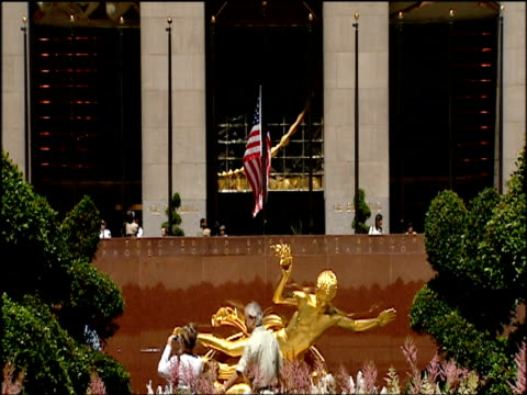 tilt up from gold statue in plaza to art deco relief above entrance to rockefeller center manhattan - beneficenza video stock e b–roll