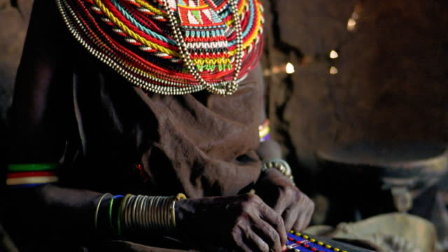ms tilt up from hands of senior masai tribeswoman beading to her face looking down / kenya - masai stock videos and b-roll footage