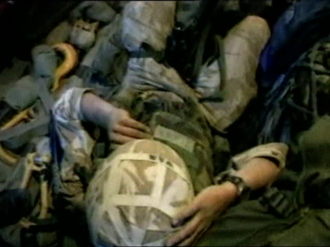 tilt up from helmet of soldier to reveal troops cramped in hold of helicopter during iraq war 25 mar 03 - 軍用輸送車点の映像素材/bロール