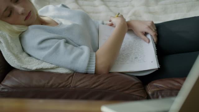 tilt up from laptop to girl who fell asleep on sofa doing homework / highland, utah, united states - endast en tonårsflicka bildbanksvideor och videomaterial från bakom kulisserna