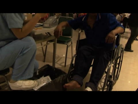 tilt up from legs of rescued victim sitting alongside others in makeshift rescue center following typhoon morakot taiwan 12 august 2009 - taiwan stock videos & royalty-free footage