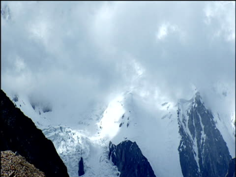 Tilt up from mountain pass past clouds to summit of K2