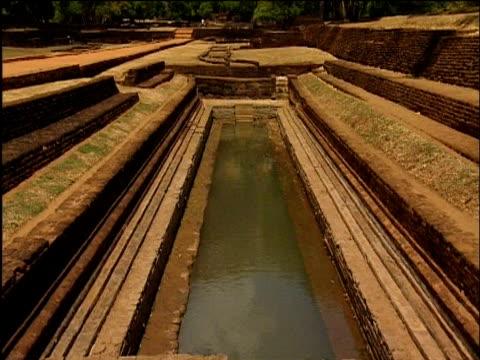 Tilt up from pool to Lion Mountain of Sigiriya Sri Lanka