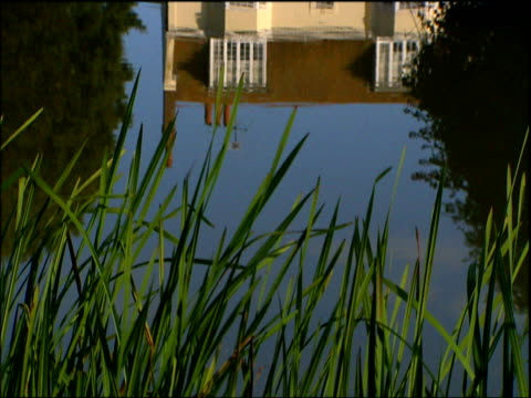 tilt up from reflection in pond to rudyard kipling's house at rottingdean sussex - 戦争記念碑点の映像素材/bロール