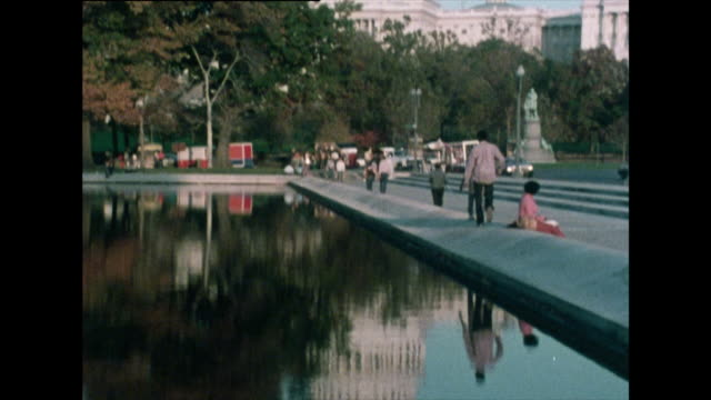 vídeos y material grabado en eventos de stock de tilt up from reflection of us capitol building in pool; 1976 - ciudades capitales