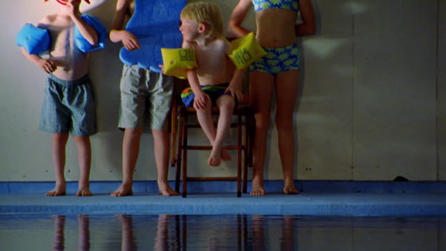 tilt up pan from reflection to portrait 4 children in swimsuits with swimming gear on side of indoor pool - schwimmflügel stock-videos und b-roll-filmmaterial