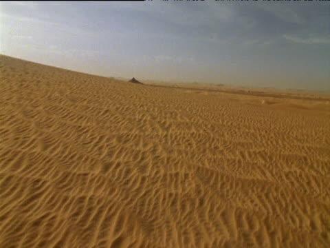 Tilt up from sand to camel train walking across Sahara Desert