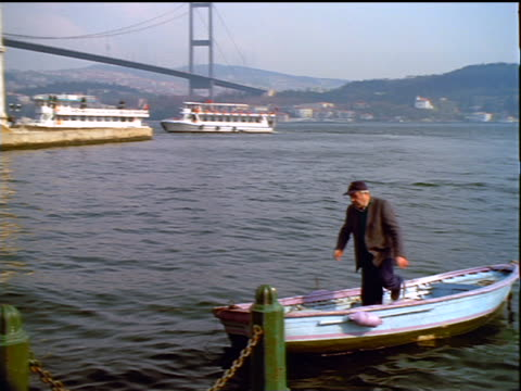 tilt up pan from senior man in rowboat to ortakoy mosque with bosporus bridge in background / istanbul - july 15 martyrs' bridge stock videos & royalty-free footage